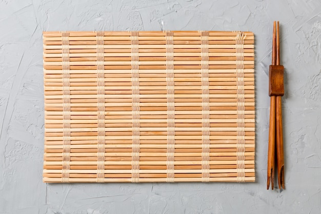 Zwei sushi-stäbchen mit leerer bambusmatte oder holzplatte Premium Fotos