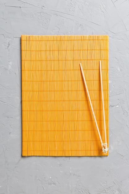 Zwei sushi-trainingsstöcke mit leerer bambusmatte oder holzplatte Premium Fotos