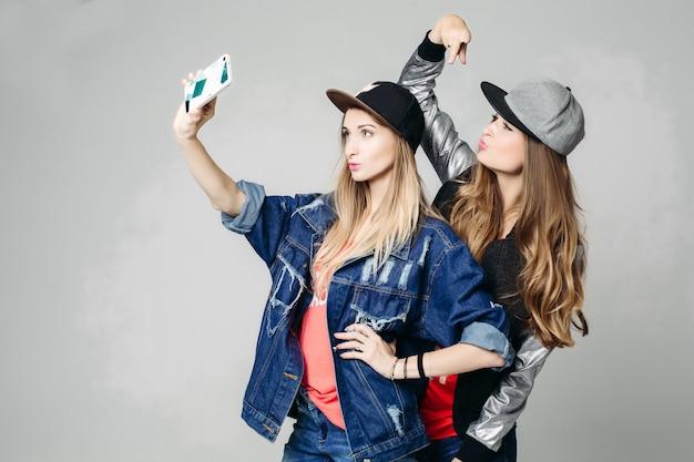 Zwei swagschwestern, die selbstporträt am anruftelefon nehmen. Premium Fotos