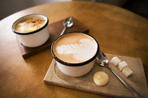 Zwei tassen cappuccino und latte stehen auf einem holztisch Premium Fotos