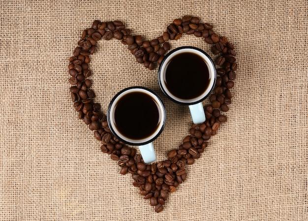 Zwei tassen espresso in einem herzförmigen kaffeebohnen. Kostenlose Fotos