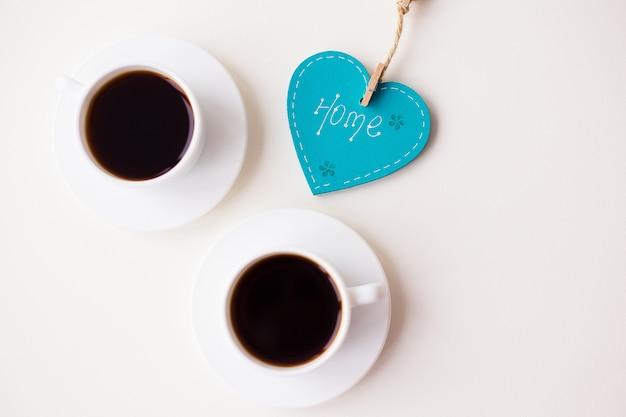Zwei tassen kaffee auf dem tisch und ein herz Premium Fotos