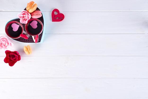 Zwei tassen kaffee, makronen, blumen in einer kastenform eines herzens auf einem weißen hintergrund. Premium Fotos