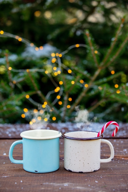 Zwei tassen kaffee mit lichterketten und kiefer Premium Fotos