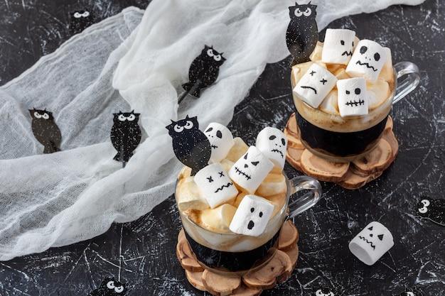 Zwei tassen kaffee mit marshmallow (gruselige gesichter, monster) auf dunklem tisch für halloween Premium Fotos