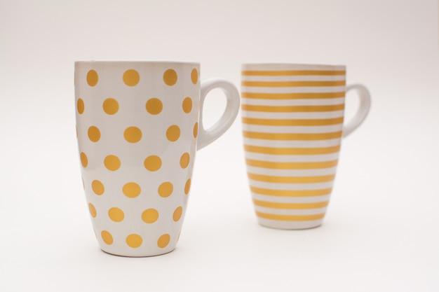 Zwei tassen kaffee stehen zusammen. tassen für kaffee mit einem muster in form von kreisen und streifen Premium Fotos