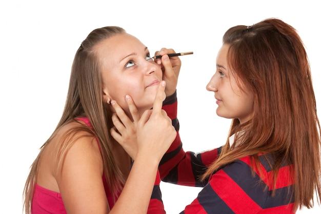 Zwei teenager färben ihre wimpern isoliert Premium Fotos