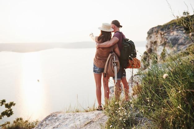 Zwei touristische männer und frauen mit rucksäcken stehen oben auf dem felsen und genießen den sonnenaufgang. Kostenlose Fotos