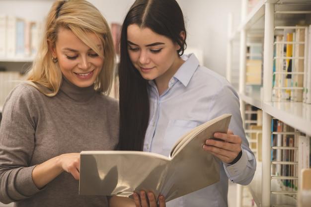 Zwei weibliche collegefreunde, die ein buch an der bibliothek studieren Premium Fotos