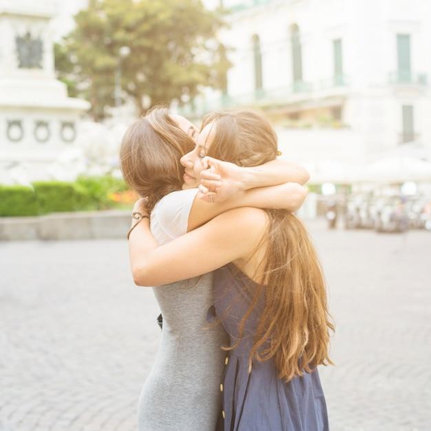 Zwei weibliche freunde, die sich an draußen umarmen Kostenlose Fotos