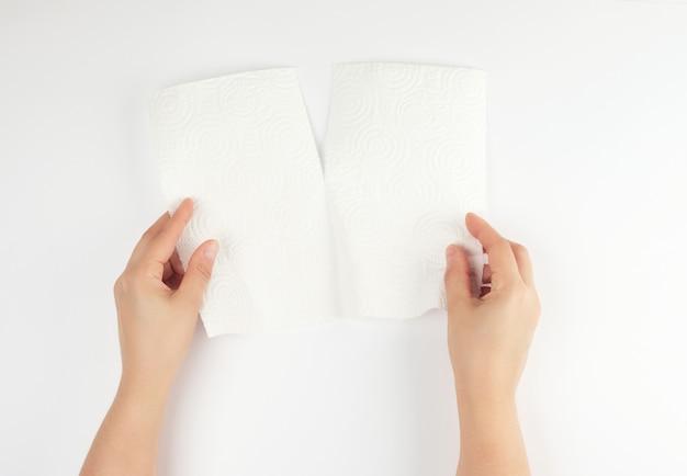 Zwei weibliche hände, die eine saubere weißbuchserviette für gesicht und körper halten Premium Fotos