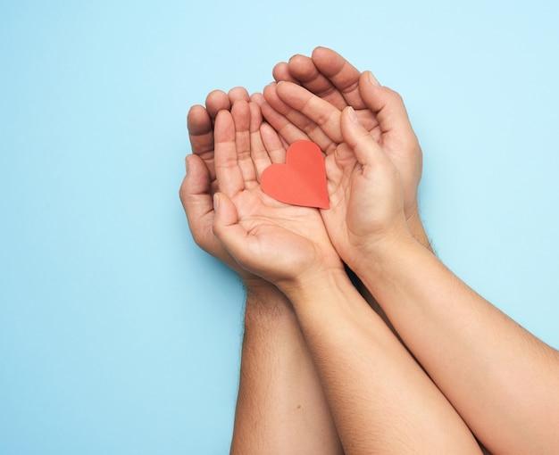Zwei weibliche hände liegen in männlichen handflächen und halten ein rotes papierherz, draufsicht. konzept von freundlichkeit, liebe und spende Premium Fotos