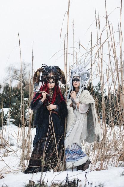 Zwei weibliche hexen in fantasiekleidung und kronen, die im winterschnee stehen Premium Fotos