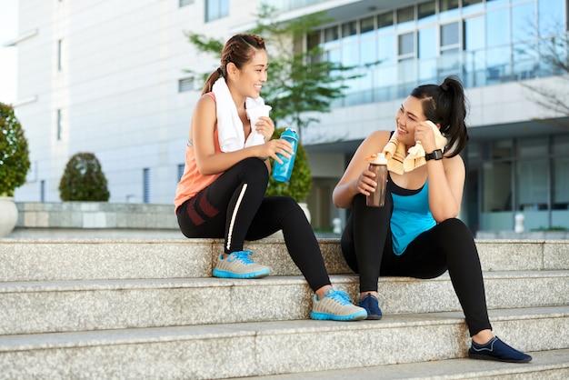 Zwei weibliche rüttler, die auf treppenhaus mit sportflaschen sitzen und nach training stillstehen Kostenlose Fotos