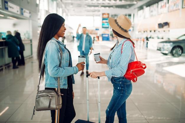 Zwei weibliche touristen treffen eine freundin am flughafen Premium Fotos