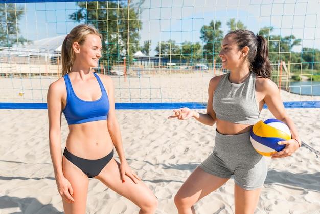 Zwei weibliche volleyballspieler am strand mit netz dahinter Kostenlose Fotos