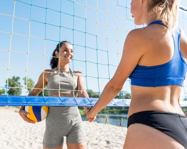 Zwei weibliche volleyballspieler mit ball und netz am strand Kostenlose Fotos