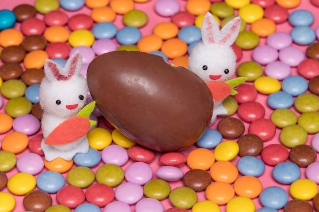 Zwei weiße häschen mit schokoladenosterei auf bunten edelsteinsüßigkeiten Kostenlose Fotos