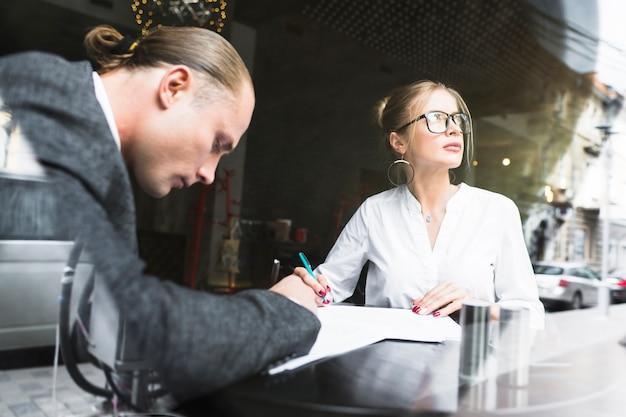 Zwei wirtschaftler, die an dokument im restaurant arbeiten Kostenlose Fotos