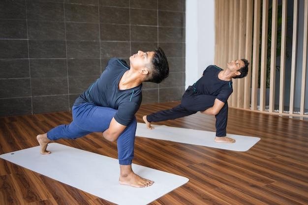 Zwei yogis, die drehte seitenwinkelhaltung in der turnhalle tun Kostenlose Fotos