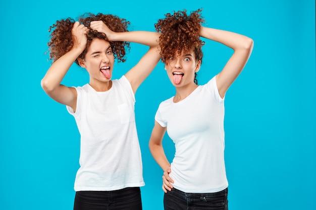 Zwei zwillinge der frau halten haare und scherzen über blau. Kostenlose Fotos
