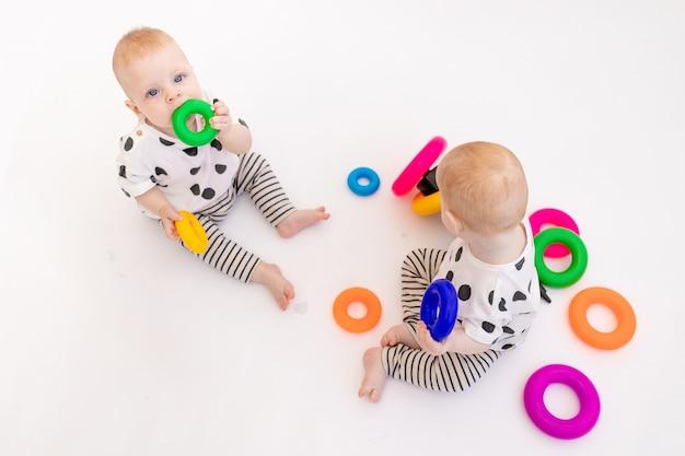 Zwei zwillingsbabys spielen auf einem weißen isolierten hintergrund, frühe entwicklung von kindern bis zu einem jahr alt, ein ort für text Premium Fotos