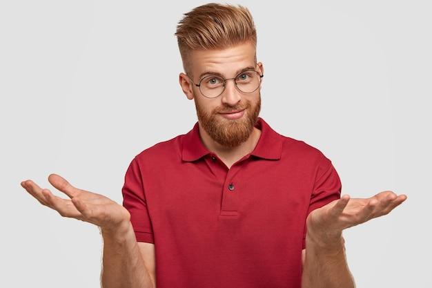 Zweifelhafter attraktiver bärtiger junger mann mit ingwerhaar, dickem bart und schnurrbart, zuckt mit den schultern, zweifelt daran, was er kaufen soll, sieht ansprechend aus und posiert an der weißen wand. zögern konzept Kostenlose Fotos