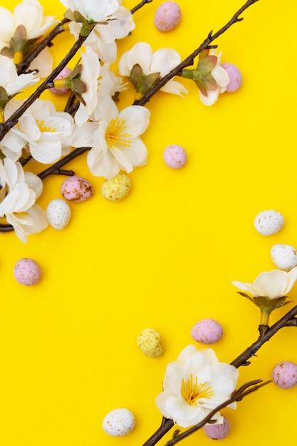 Zweig der weißen blumen auf gelbem hintergrund mit süßigkeit, osterschokolade ärgert. ostern verspotten. minimalistic frühlingshintergrund. Premium Fotos