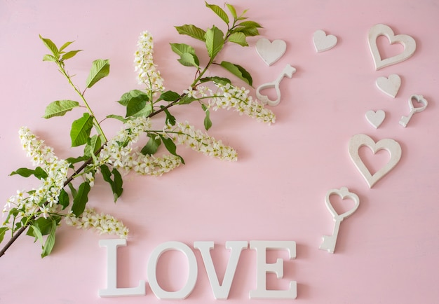 Zweig der weißen vogelkirsche, herzen, schlüssel auf einem rosa hintergrund Premium Fotos
