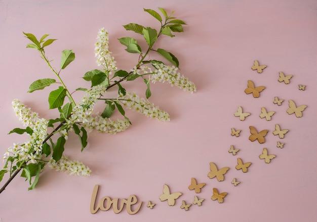 Zweig der weißen vogelkirsche und der schmetterlinge auf einem rosa hintergrund Premium Fotos
