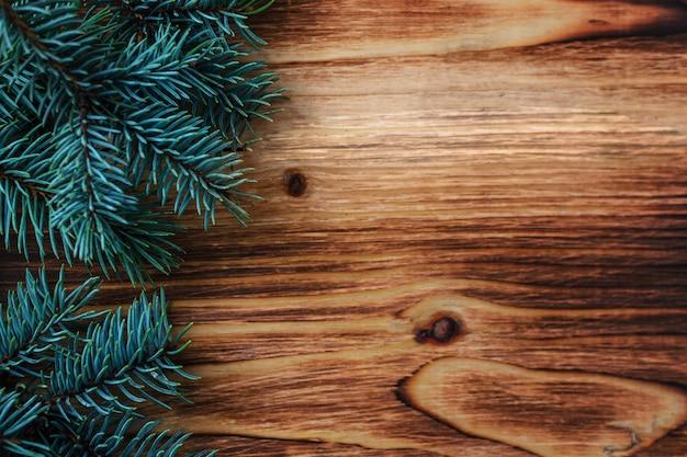Zweig des weihnachtsbaums auf einem hölzernen hintergrund Premium Fotos