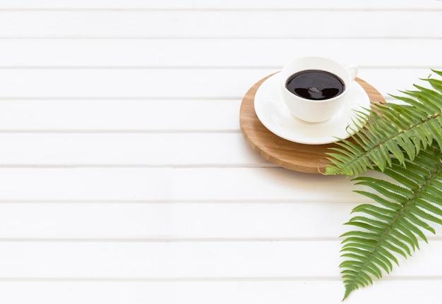Zweige des grünen eukalyptus, des farns und der tasse schwarzen kaffees auf dem hintergrund einer tafel der weißen bretter mit einem leeren textplatz in der mitte Kostenlose Fotos
