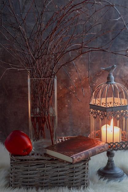 Zweige einer birke in einer vase, einem kerzenständer mit einer kerze, einem buch und einem roten apfel auf grauem hintergrund Premium Fotos