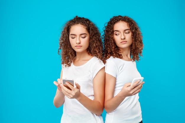 Zwillinge zweier frauen, die telefone über blau betrachten. Kostenlose Fotos