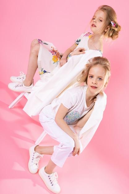 Zwillingsmädchen in der hellen kleidungsaufstellung Premium Fotos