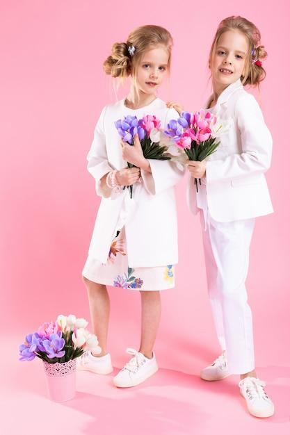 Zwillingsmädchen in leichter kleidung mit blumensträußen stehen auf rosa. Premium Fotos