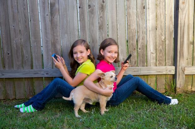 Zwillingsschwestermädchen, die smartphone und chihuahuahund spielen Premium Fotos