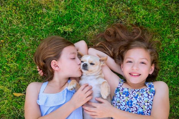 Zwillingsschwestern, die mit dem chihuahuahund liegen auf rasen liegen Premium Fotos