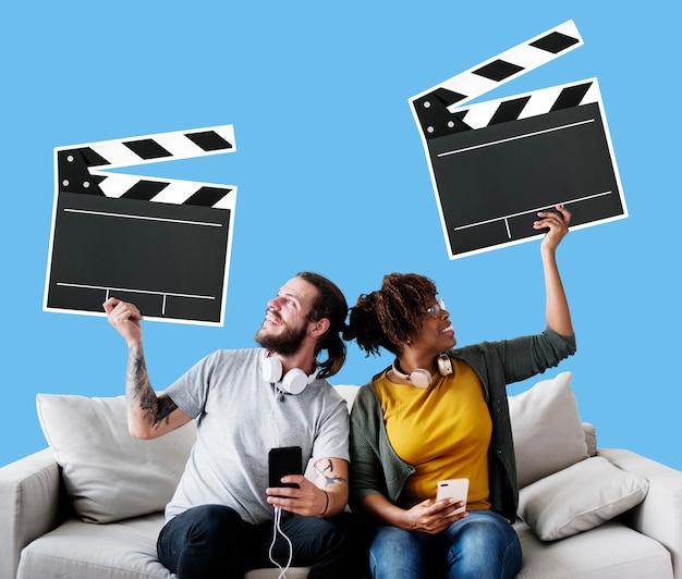 Zwischen verschiedenen rassen paare auf einer couch, die scharnierventilikonen hält Kostenlose Fotos