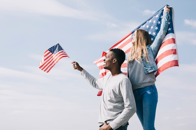 Zwischen verschiedenen rassen patrioten, die flaggen als freiheitssymbol wellenartig bewegen Kostenlose Fotos