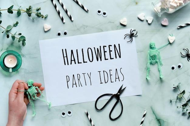 Zwischenablage mit text halloween party ideen auf mintgrünem hintergrund. flach lag mit dem skelett in der hand, Premium Fotos