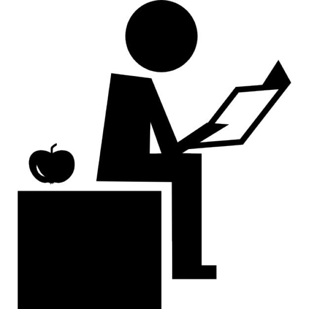 Teacher reading sitting on his desktop with an apple on ...