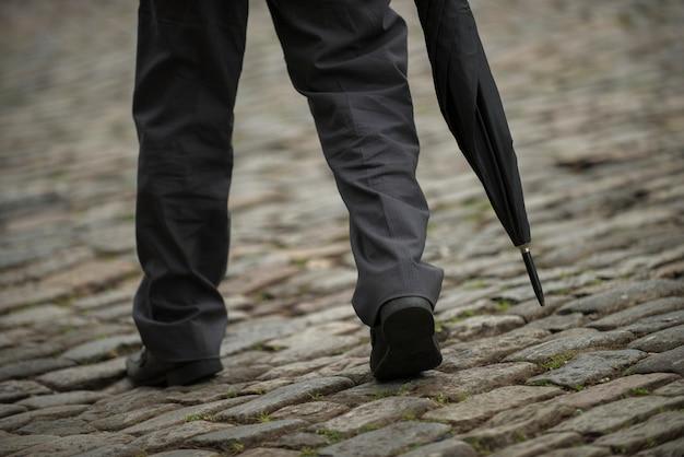 Ору-прету, минас-жерайс, бразилия - 02 февраля 2016: мужчина держит зонтик, спускаясь по склону Premium Фотографии