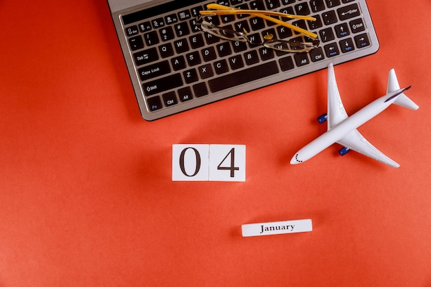 04 january calendar with accessories on business workspace office desk on computer keyboard, airplane, glasses red background Premium Photo