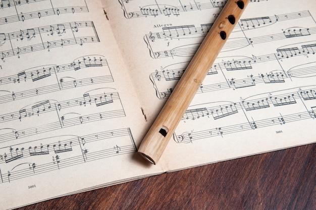 07-06-2020 баку.азербайджан. винтажная бамбуковая флейта поверх старинных музыкальных нот Premium Фотографии