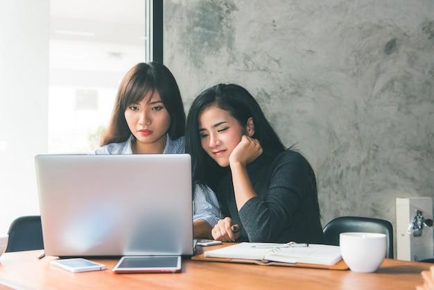 1対1のミーティング。カフェのテーブルに座っている2人の若いビジネス女性。女の子は、ノートパソコンの画面に同僚の情報を示しています。スマートフォンのブログを使っている少女。チームワークビジネスミーティング。フリーランスは働いています。 無料写真