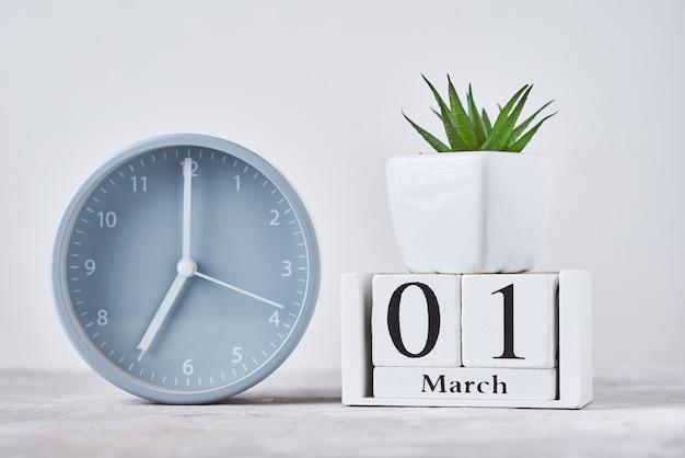 木製ブロックカレンダー日付目覚まし時計1月3日とテーブルの上の植物 Premium写真