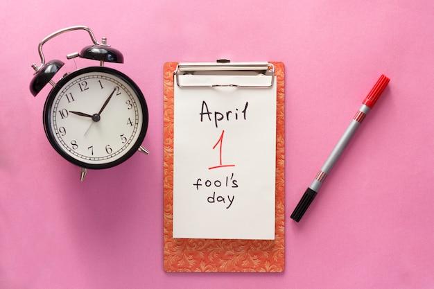 1月4日の愚か者の日、ノート、時計、ペン。ピンクの背景にフラットを置きます。 Premium写真