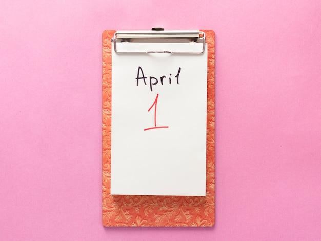 1月4日の愚か者の日、ノート。ピンクの背景にフラットを置きます。 Premium写真