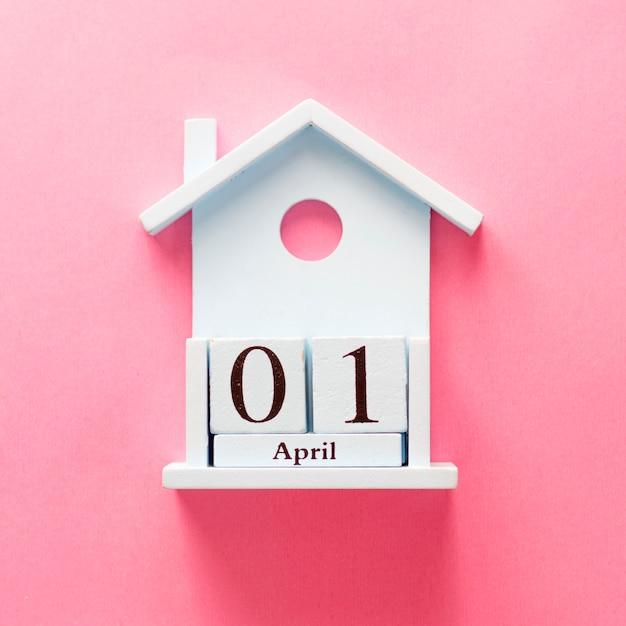 木製カレンダー1 4月のばかの日。ピンクの背景にフラットを置きます。 Premium写真